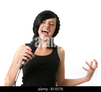 A girl sings and gestures with a microphone in her hand - Stock Photo
