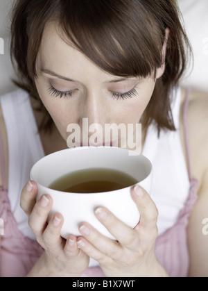 Frau trinkt aus einer Schale - Stock Photo