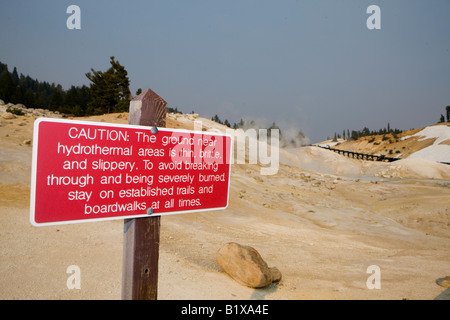 A red caution sign warns visitors to say on the boardwalk to avoid damage to the hydrothermal areas in Bumpass Hell - Stock Photo