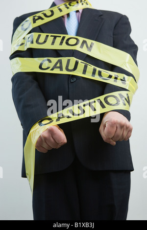Mid section view of a businessman wrapped in a Caution tape - Stock Photo