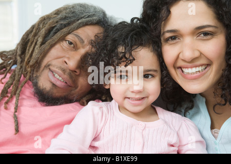Portrait of a mid adult couple smiling with their daughter - Stock Photo
