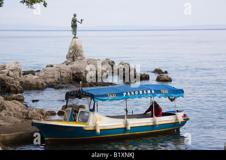 Opatija Istria Croatia Europe May Water taxi boat on rocky shore by Maiden with the Seagull statue on Kvarner Gulf - Stock Photo