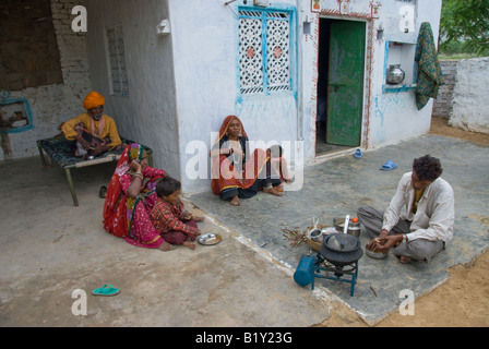 Family cooking food in courtyard of a house in Rajasthan, India. - Stock Photo