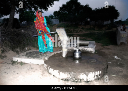 Woman from Rajasthan fetches water at the handpump in the village. In the evening there is no line and her work - Stock Photo