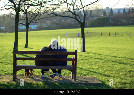 An elderly couple sit on a park bench, enjoying the view and taking life in their stride. - Stock Photo