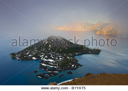 Thick fog seems to originate from the volcanic cone of Wizard Island located in Crater Lake, Oregon. - Stock Photo