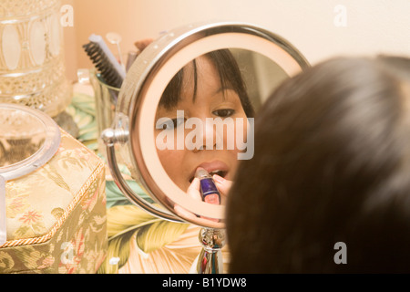 a young asian woman doing her hair and makeup - Stock Photo