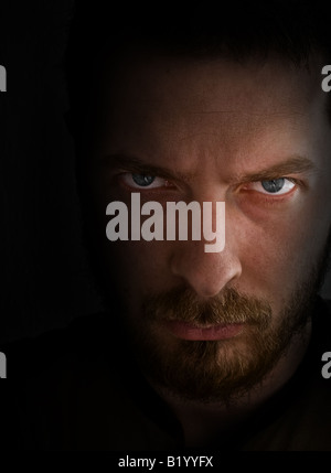 Face of angry evil looking man in the dark - Stock Photo