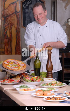 Pizza Chef in Italian restaurant with selection of dishes - Stock Photo