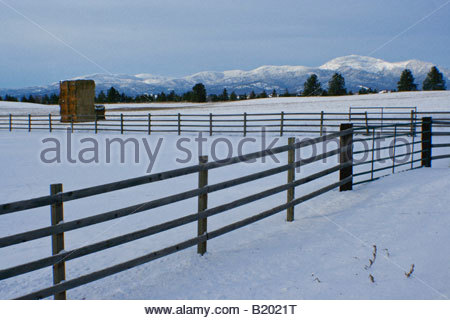 A fence through a snowy Pasture on the Rathdrum Prairie with hay bales and the snow capped Rathdrum Mountain in - Stock Photo