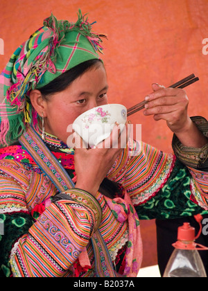 Flower Hmong woman with chopsticks in the market of Bac Ha Vietnam - Stock Photo