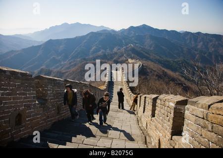 Tourists walk the ancient Great Wall of China at Mutianyu north of Beijing formerly Peking China - Stock Photo