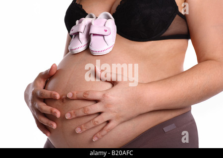 Pregnant woman with little baby shoes on her belly - Stock Photo