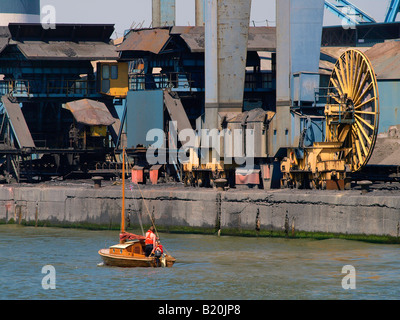 Small vintage wooden sailing boat yacht sailing past the huge machines in the seaport of Antwerp Flanders Belgium - Stock Photo