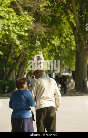SPAIN Madrid Mature couple walk arm in arm in Paseo del Prado park area Trees in urban green space - Stock Photo