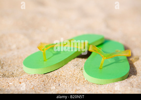Pair of green flip flops  on the beach. - Stock Photo