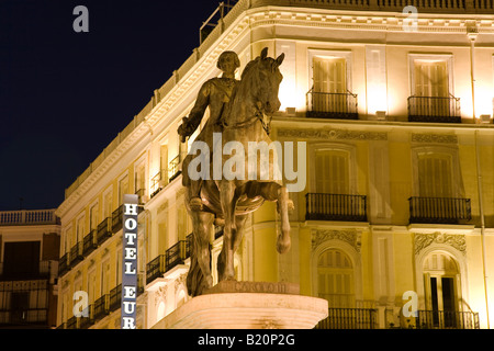 SPAIN Madrid Statue of Mounted King Charles III in Puerto del Sol plaza at night lit hotel building in background - Stock Photo