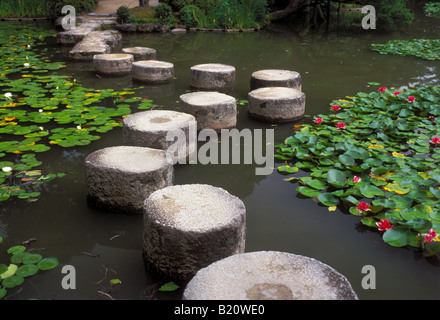 Stepping stones lead across a garden lily pond at the Heian Jungu shrine in Kyoto. - Stock Photo