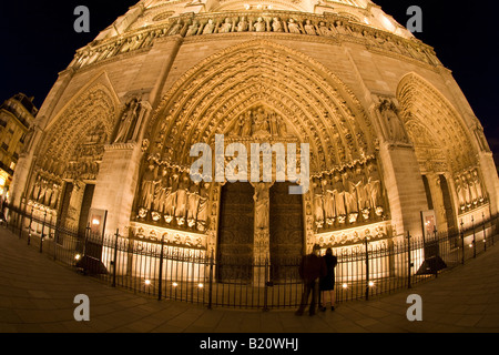Couple in front of Notre Dame Cathedral west facade floodlit illuminated illuminations in evening night light Paris - Stock Photo