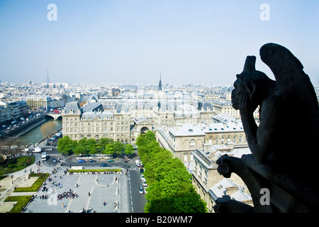 Notre Dame Cathedral gargoyles on exterior with scenic panoramic view over Paris in spring sunshine France Europe - Stock Photo