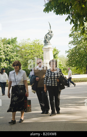 SPAIN Madrid Spanish adults walk on sidewalk through gardens in Retiro Park Parque del Buen Retiro near fountain - Stock Photo