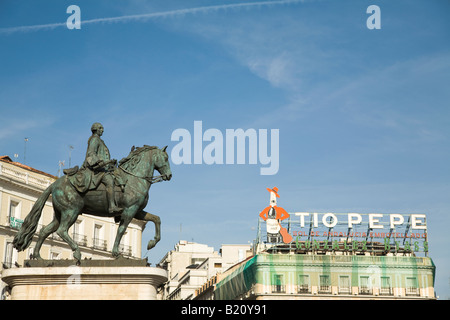 SPAIN Madrid Statue of Mounted King Charles III in Puerto del Sol plaza with Tio Pepe sign - Stock Photo