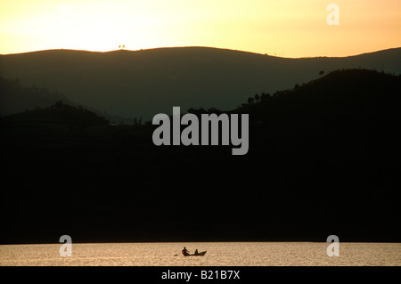 Two local men in a wooden dugout canoe paddeling across Lake Bunyonyi in silhouette at sunset. - Stock Photo