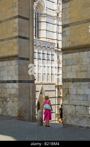 Girl in a pink dress looking through the entrance to the Piazza del Duomo, Siena, Italy - Stock Photo