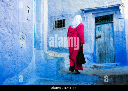 Chefchaouen woman in traditional dress in the old town with typical blue painted houses - Stock Photo
