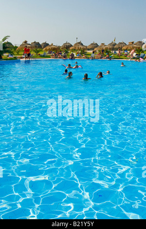 Vertical wide angle of a busy hotel swimming pool surrounded by lots of grass parasols and sunbeds - Stock Photo