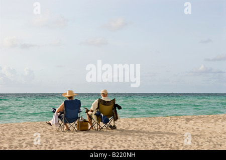 Couple relaxing on Miami Beach in the morning - Stock Photo