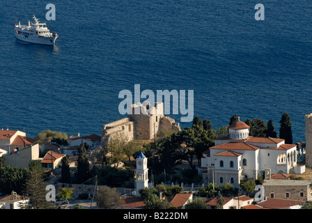 Greek castle, church and houses on a hill above the blue sea with a motor yacht in the background. - Stock Photo