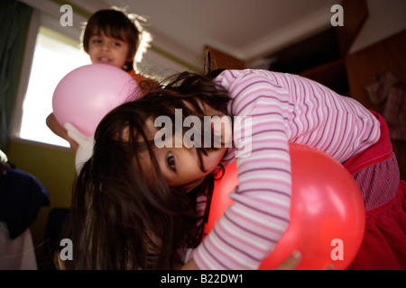Boy aged six and sister aged four play with balloons in their bedroom. Mixed race asian english - Stock Photo