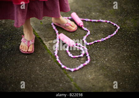 Girl aged four learning to skip Note trademarked Disney skipping rope - Stock Photo
