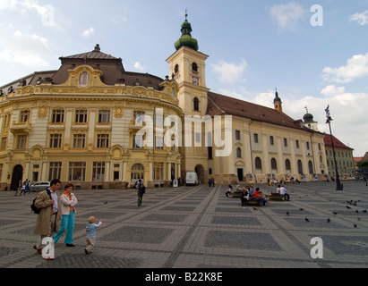Palace and church on a square in the center of a town. Piata Mare, Sibiu, Romania - Stock Photo