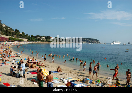 Locals and Tourists enjoy the late afternoon sun on the golden sands of Villefranche, France - Stock Photo