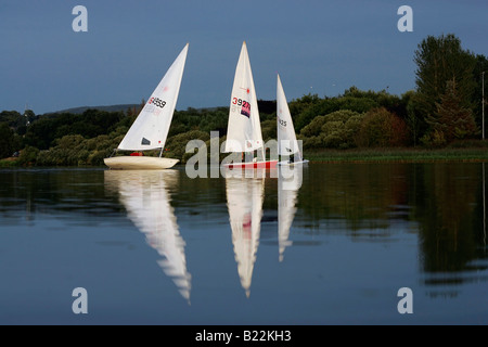 Sailing boats jostle for position during a sailing club's race on a particularly calm evening. - Stock Photo
