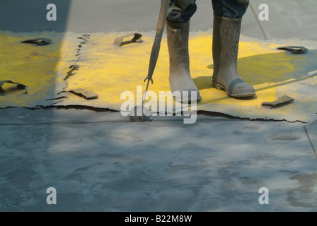 A workman stands on a texture stamp as he uses a trowel to finish a line in the concrete driveway of a home in California. - Stock Photo
