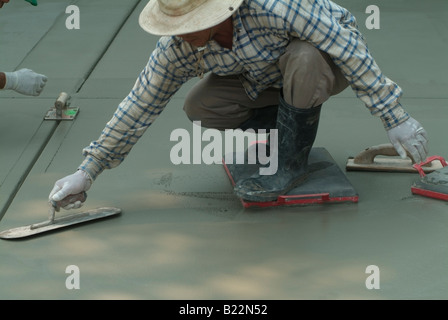 Workman leveling wet concrete with a Darby while another workman uses an edging tool to groove freshly poured concrete - Stock Photo