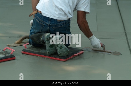 Workman leveling wet concrete with a Darby during construction of a driveway in front of a private home in California. - Stock Photo