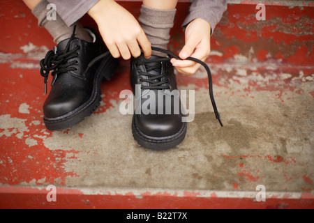 Six year old boy tries to tie laces on his new shoes - Stock Photo