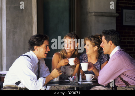 Two young couples talking to each other in cafe - Stock Photo