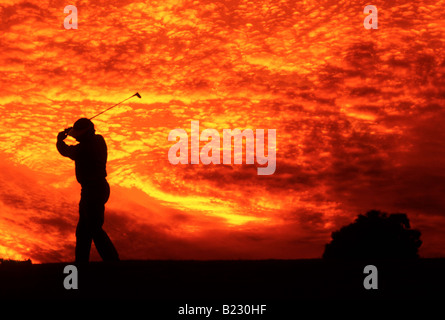 Silhouette of golfer at dusk - Stock Photo
