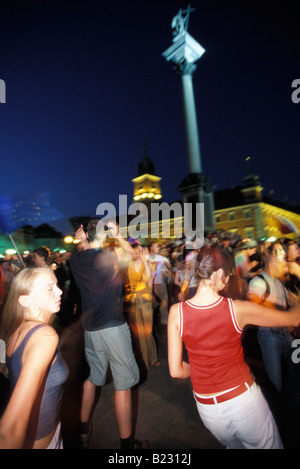 Young people dancing in a square in the Old Town with the Royal Palace and Sigismund Statue in the background Warsaw - Stock Photo