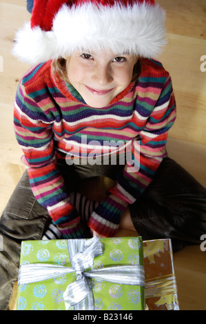 Portrait of girl sitting with christmas gifts on floor and smiling - Stock Photo