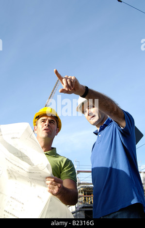 Low angle view of two male architects at construction site - Stock Photo