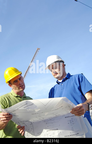 Low angle view of two male architects looking at blueprints - Stock Photo