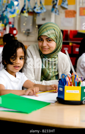 Young Muslim teacher over looks a child learning - Stock Photo
