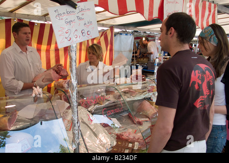 Couple buying food from a butcher's stall at a food market in central Paris - Stock Photo