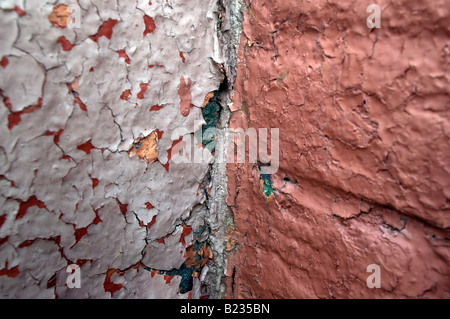 Close up of peeling lavender and red paint on a wall - Stock Photo